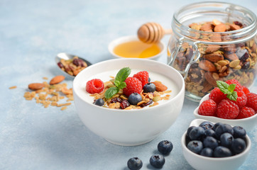 Homemade granola with yogurt and fresh berries, healthy breakfast concept, selective focus.