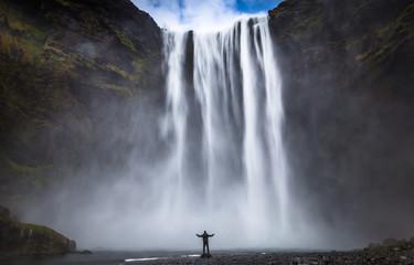 Skogafoss - May 04, 2018: Adventurer at the massive Skogafoss waterfall, Iceland Wall mural