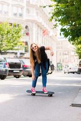 PORTRAIT OF A TEENAGE GIRL DRIVING SKATEBOARD ON THE STREET