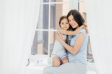Lovely small child with pleasant appearance embraces her mother, expresses love and good feeling or attitude, sit on window sill, enjoy domestic atmosphere and togetherness. Parenthood concept