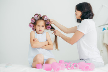 Displeased child keeps hands crossed, looks with sullen expression, being discontent as her mother winds curlers on her hair, doesn`t want to have curly hairstyle, pose against white background