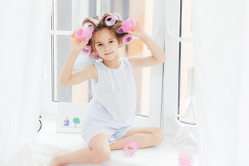 Photo of adorable cute girl with curlers on hair, sits on window sill at home, going to have curly hairstyle, wears casual clothes, looks directly into camera. Children, leisure and beauty concept
