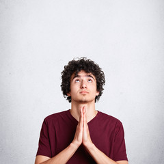Vertical shot of pleasant looking miserable male prays for something, looks upwards with great hope, asks for health, poses against white background with blank space for your advertising content
