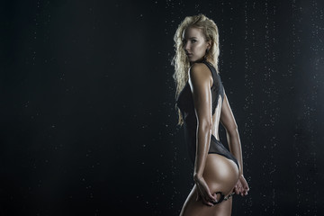 Beautiful shapely athletic big breasted blonde girl with wet oiled body wearing black translucent sexy bodysuit under falling water drops holds handcuffs in her hands on black