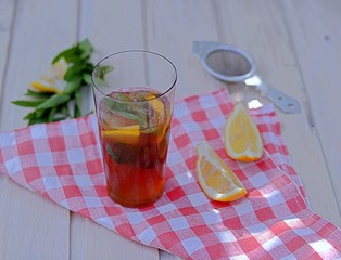 Cool drink, cold black tea with lemon, mint and ice in tall glasses. Summer concept