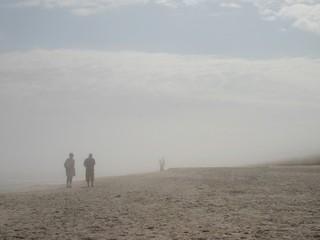 Para starszych ludzi spogląda na młodą parę we mgle na plaży.