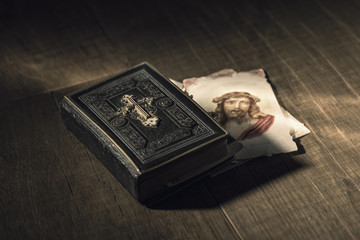 Sacred bible and Holy card with Jesus Christ image on a desk