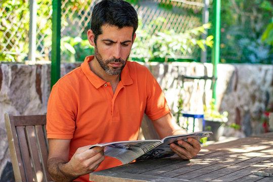 Hombre joven leyendo revista en jardín y mesa de madera. Lleva barba y polo verde