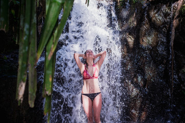 laughing girl bathing in the forest waterfall