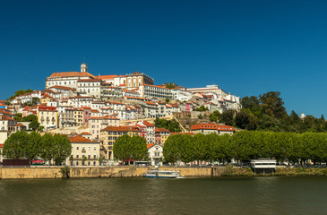 View of Coimbra, in Portugal, on a sunny day, with Mondego River on the foreground.