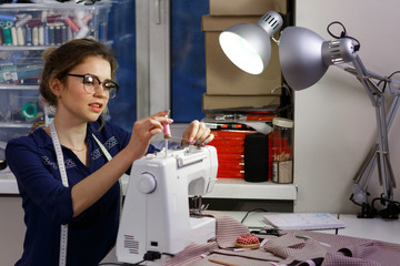 A young dressmaker woman sews clothes on a sewing machine. Smiling seamstress in his workshop