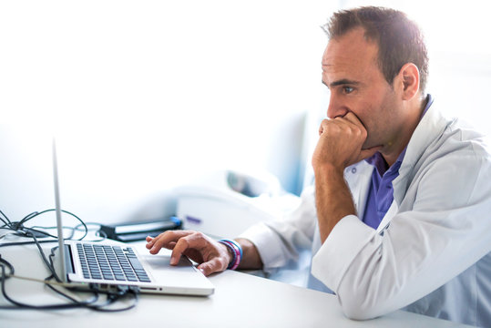 Adult man pharmacist in pharmacy working with his laptop
