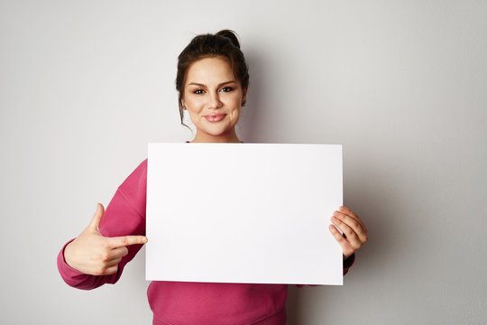 Pretty smiling woman in pink hoody holding empty blank board isolated on the gray background
