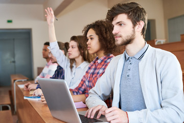 Group of students sitting at lesson in a row with laptop