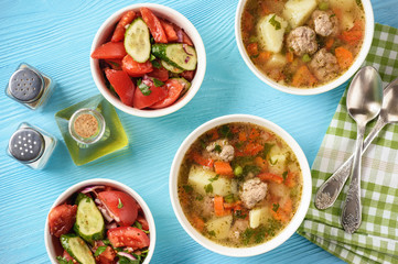 Vegetable soup with meatballs and tomato salad.