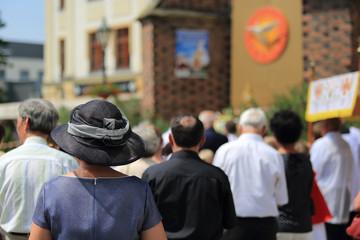 Kobieta w kapeluszu i zgromadzeni ludzie w czasie  nabożeństwa Bożego Ciała w Brzegu.