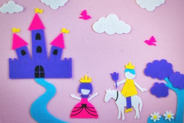 Cute fairy tale scene in felt with a princess and a prince in love in front of a fantasy castle
