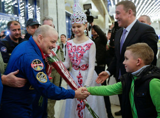 ISS crew member Tingle of the U.S. shakes hands with a boy during a welcoming ceremony at the airport in Karaganda
