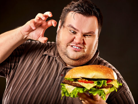 Diet failure of fat man eat fast food. Breakfast for mad overweight person who eating huge hamburger. Junk meal leads to obesity concept on black background. Feast for occasion.