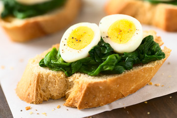 Crostini roasted bread slices with cooked spinach leaves and hard boiled quail eggs seasoned with black pepper, photographed with natural light (Selective Focus, Focus on the front of the egg yolks)
