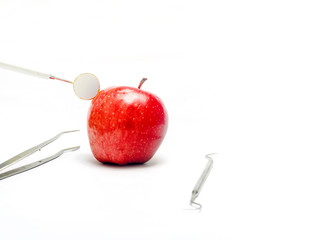 Dental mirror and probe and tweezer with fresh apple isolated in white background
