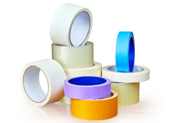 Adhesive tape in stock is stacked on white.