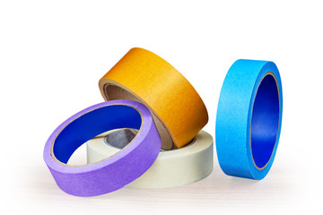Blue, purple and yellow rollers of adhesive tape on white.