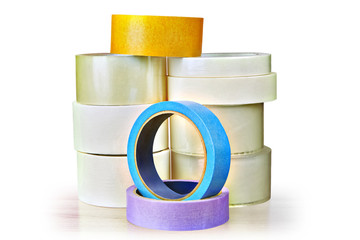 Many rolls of adhesive tape stacked pile on white background.