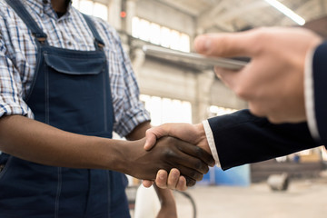 Close-up shot of unrecognizable African American worker wearing overall and checked shirt greeting investor with firm handshake,  interior of production department on background