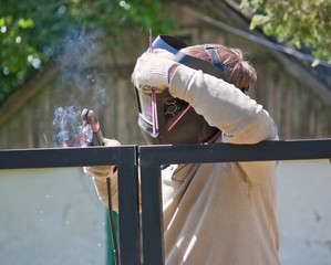 Male welder mounts the fence. Man in protective mask
