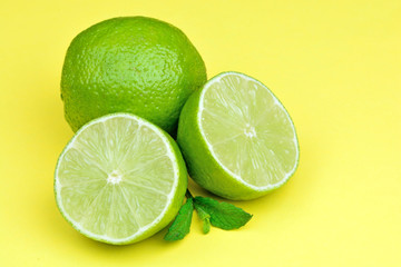 Fresh limes on yellow background