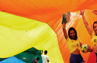 Revellers wearing Brazilian soccer player Neymar's shirts dance under a rainbow flag during the Gay Pride parade along Paulista Avenue in Sao Paulo
