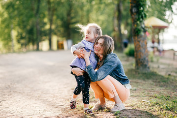 Happy smiling mother hugging her lovely little daughter outdoor. Lifestyle family. Adult cheerful female parent playing with her beautiful emotional child at nature in summer. Positive people faces.