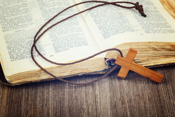 Ancient holy book of a wooden cross on a cord.