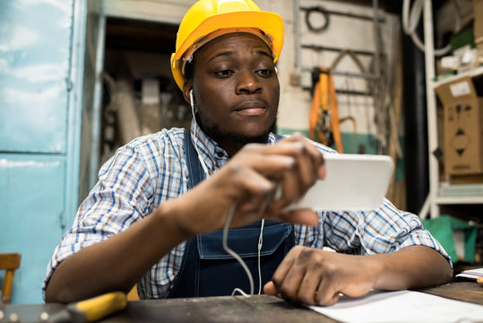 Portrait shot of African American lathe operator sitting at work bench and watching educational video on smartphone, interior of production department on background