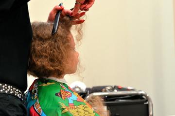 Junge lässt sich beim Friseur die langen gelockten Haare schneiden