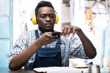 Portrait shot of handsome African American lathe operator taking picture of detail drawing on smartphone while sitting at work bench, interior of production department on background