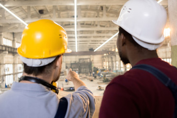 Rear view of bearded engineers wearing hardhats and overalls brainstorming on promising joint project while standing at spacious production department of modern plant with blueprint in hands.