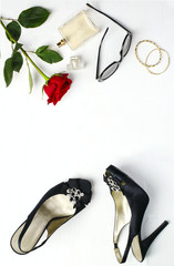 Woman fashion flatlay. Shoes, sunglasses, golden bracelets, parfume and red fresh rose  on white background. Flat lay, top view.