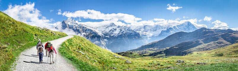 Foto auf Leinwand Gebirge Gruppe beim Wandern in den Schweizer Alpen als Panorama Hintergrund