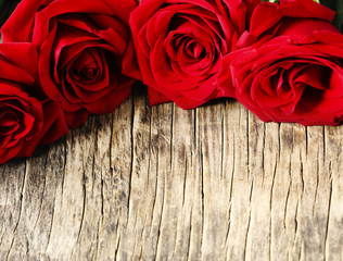 Bouquet of fresh red roses on wooden background.