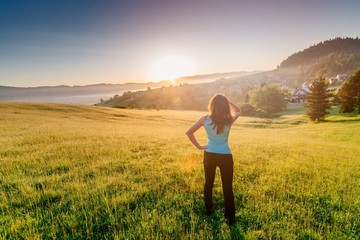 Happy girl at summer meadow enjoying beauty morning in mountains