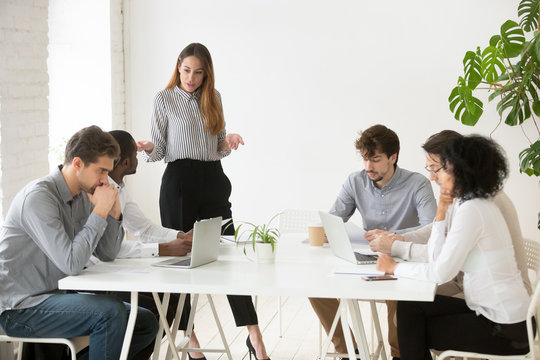 Serious businesswoman scolding employees for bad work results during company meeting, female team leader lecturing workers for poor financial rating at business briefing. Leadership concept