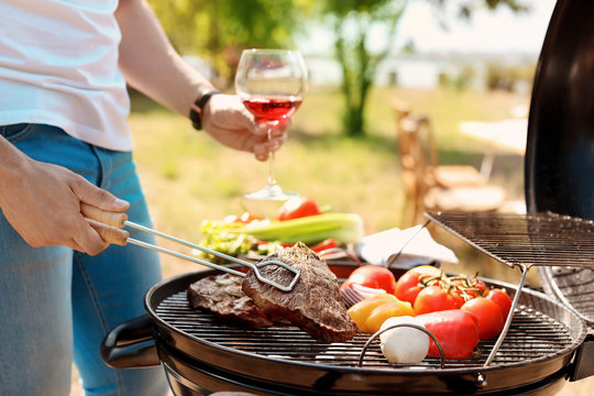 Man cooking meat and vegetables on barbecue grill outdoors