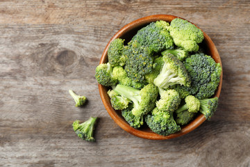 Bowl with fresh green broccoli on wooden background, top view