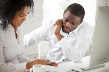 Two African American workers talking discussing business ideas, negotiating about corporate project, female black colleague explaining to male associate listening attentively. Cooperation concept