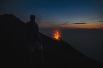 Young man watching a Stromboli volcano eruption at sunset