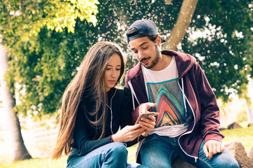 Couple browsing smartphone in park