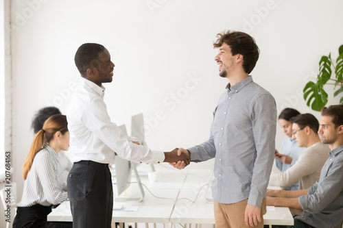 African american employer shaking hand of shy male caucasian job african american employer shaking hand of shy male caucasian job applicant congratulating with successful interview m4hsunfo
