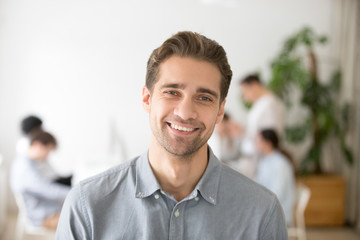 Portrait of casual smiling Caucasian male worker laughing looking at camera, positive employee posing for company business catalogue with colleagues at background, having photo shoot in office Wall mural